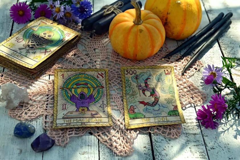 Natura mortă cu dovleci, cărți de tarot și lumânări negre pe șervețel vechi cu broderie