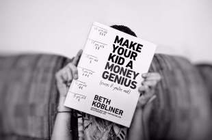 girl holding a copy of the book Make Your Kid a Money Genius over her face