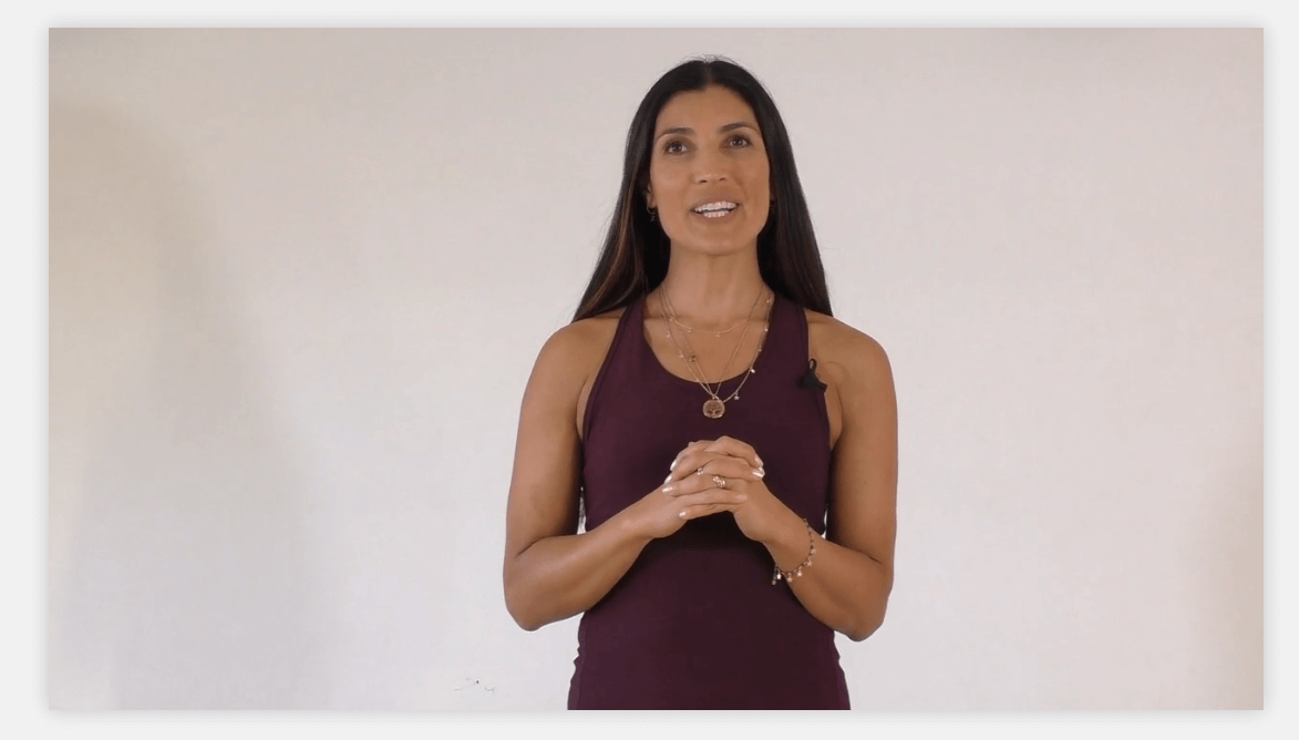 A screenshot showing a female yoga instructor talking in a video.