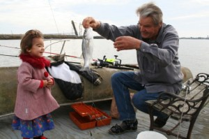 Grandfather fishing with girl