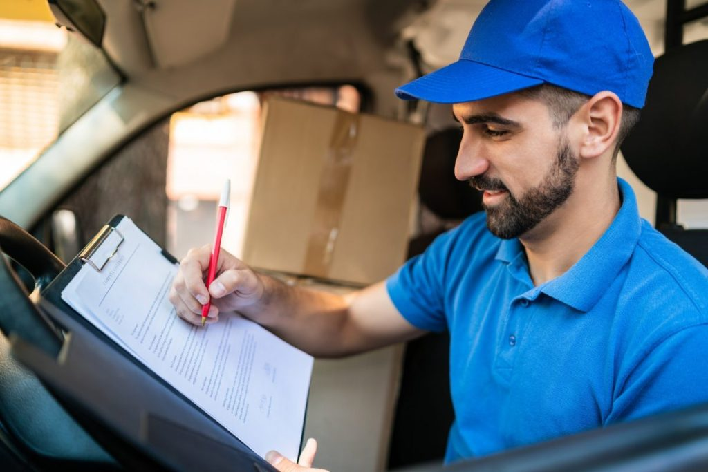 Delivery man checking delivery list in van.