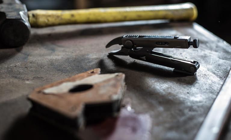 Leatherman crunch multi-tool on wooden table, black