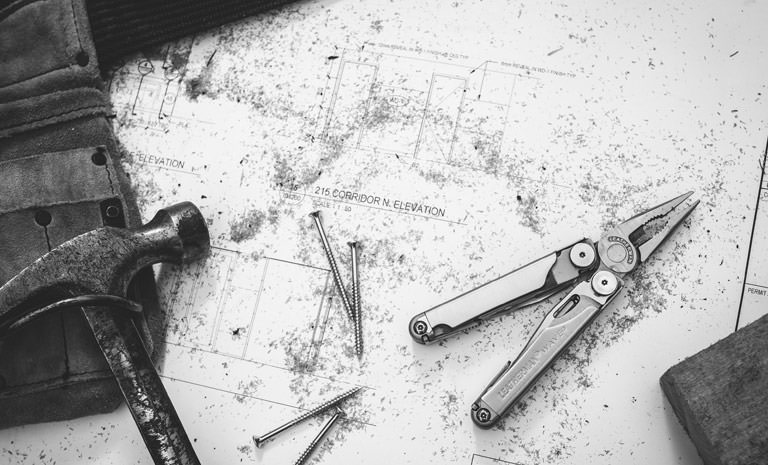 Leatherman black & silver wave multi-tool open and ready, next to hammer and nails