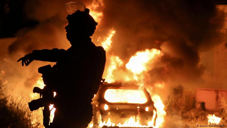 Israel security forces burn a car in Palestine amidst Gaza conflict.