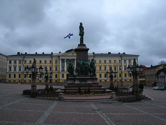 Some statues in the middle of the square, and the Finnish flag.