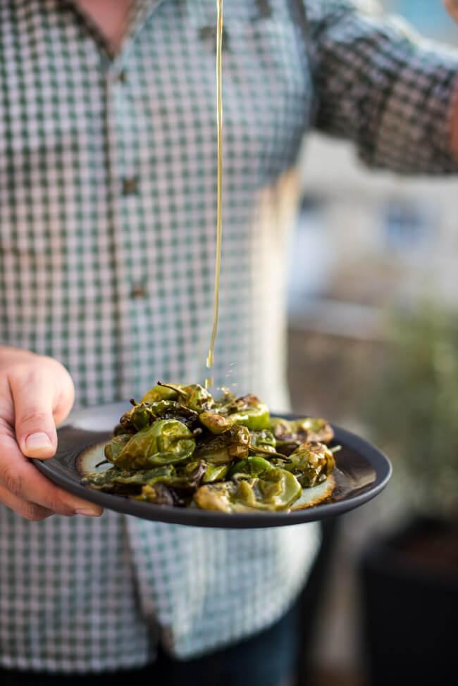 Männerhände halten Teller mit Pimientos de Padrón und gießen Olivenöl darüber