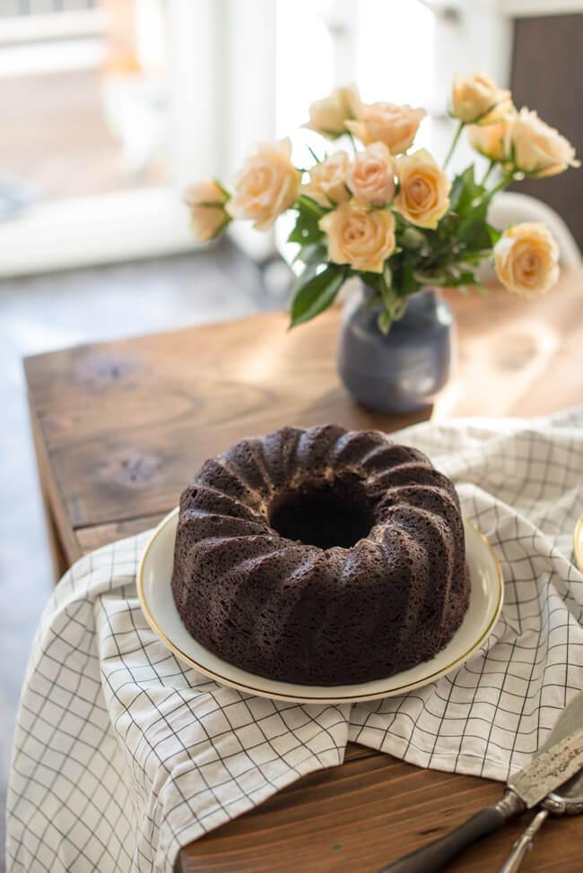 Brownie Gugelhupf mit Cheesecake Swirl und einer Vase mit Rosen auf einem Tisch