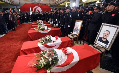 Presidential guards mourn around the coffins of their comrades who were killed in a bomb blast on a bus in central Tunis the previous day during a official ceremony to honour them at Carthage Palace in the Tunisian capital on November 25, 2015. The Islamic State group claimed the deadly bombing of a presidential guard bus in the Tunisian capital in a statement shared on jihadist social media accounts. AFP PHOTO / FETHI BELAID