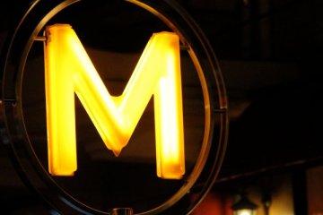Le Jour ni l'Heure 5102 : Das klar erglänzende «M», Paris, métro Vavin, devant la Rotonde, samedi 10 novembre 2012, 21:05:41