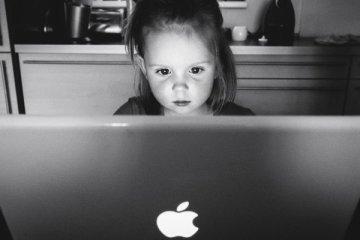 Une petite fille concentrée derrière un ordinateur Apple