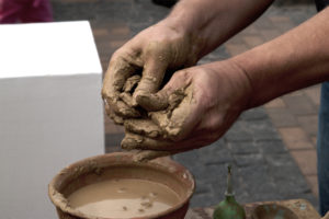 Hands working on pottery wheel , close up retro style