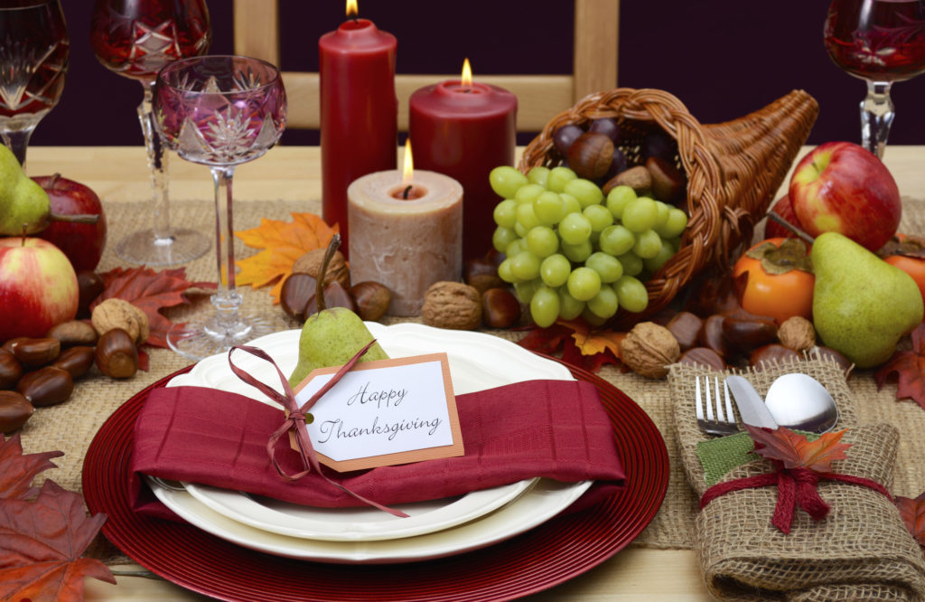 Country style rustic Thanksgiving table with place setting, cornucopia, candles and Autumn fruit centerpice.