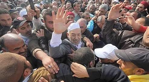 Rached Ghannouchi, le chef du mouvement islamiste tunisien Ennahda (au centre), salue la foule venu l'accueillir dimanche à l'aéroport de Tunis-Carthage.