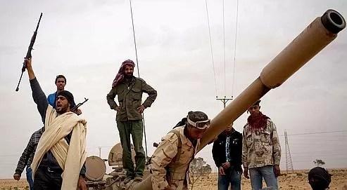 Hier à Benghazi, un rebelle exprime sa joie, grimpé sur l'épave d'un avion loyaliste abattu après avoir bombardé l'aéroport.
