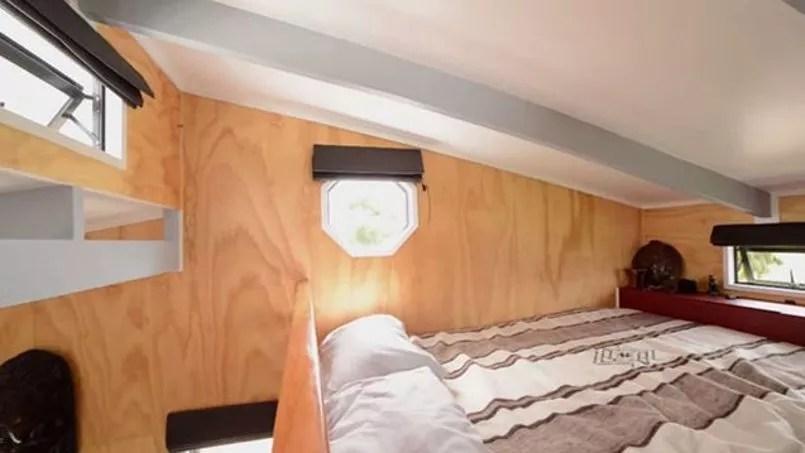 Une chambre à coucher en mezzanine, avec un lit deux places, et plusieurs ouvertures.