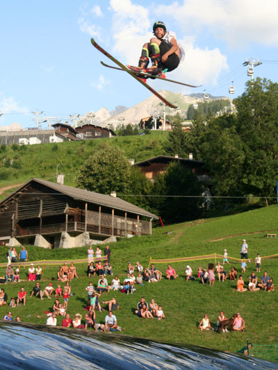 <Photo of freestyle skier with audience below, La Clusaz behind>