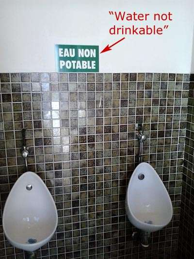 'Not drinking water' sign in French toilet.