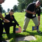 Leading candidate for National Commander Denise Rohan of Wisconsin and Department of Nevada Delegation Chairman Bob Terhune place flags at Miller's grave. Photo by Holly K. Soria/The American Legion