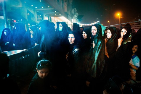 Women queue up for food at a makeshift kitchen in Najaf, Iraq. Local Iraqis offer fresh meals, water, places to sleep and many other amenities for free. Some families set aside as much as twenty percent of their annual earnings.
