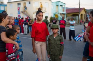 """Two young Cuban children await the funeral convoy carrying the ashes of Fidel Castro to their final destination: the cemetery of Santa Ifigenia in Santiago de Cuba, 4 December 2016. The girl has the revolutionary slogan """"Yo soy Fidel"""" (I'm Fidel) painted on her cheek and t-shirt, while her younger brother is dressed in a Cuban army uniform with a typical armband of the """"26th of July Movement"""", the day when Moncada was conquered. The """"26th of July Movement"""" was a vanguard revolutionary organization led by Fidel Castro that overthrew the Fulgencio Batista dictatorship in Cuba in 1959."""