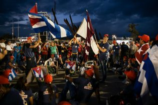 """Many Cubans shout slogans for Fidel Castro and sing national songs to commemorate the """"Lider Maximo"""" during the funeral wake in Santiago de Cuba, 3 December 2016. Many people gathered in Plaza de la Revolution square carrying Cuban flags, images of the """"Comandante"""" and lighting candles as a farewell offering, waiting for a speech by Raul Castro, the official President of Cuba."""