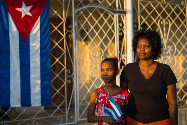 A mother and her young daughter with Cuban flags await the funeral convoy carrying the ashes of Fidel Castro to their final destination: the cemetery of Santa Ifigenia in Santiago de Cuba, 4 December 2016.
