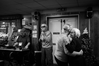 A blind man sings as a couple of old friends dance.