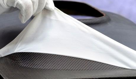 Abzug der Flexplas-Trenn- und Schutzfolie von einem kontaminationsfreien CFK-Bauteil nach Aushärtung in der Heizpresse.