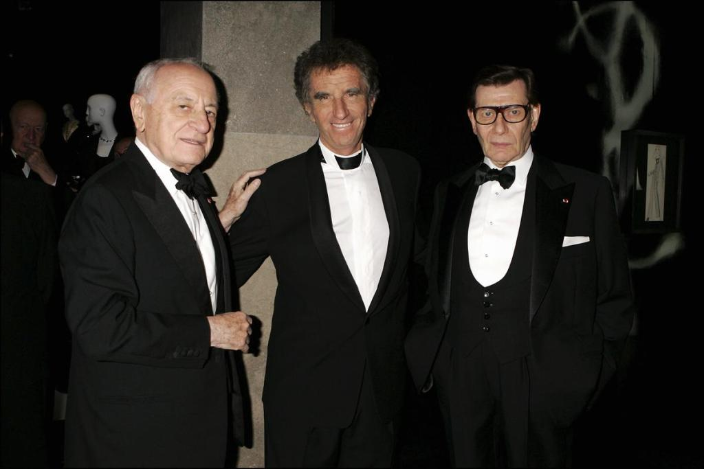 FRANCE - OCTOBER 03:  Yves Saint Laurent Smoking Forever Exhibition In Paris - On October 3Rd, 2005 - In Paris, France - Here, Pierre Berge Jack Lang Yves Saint Laurent  (Photo by Serge BENHAMOU/Gamma-Rapho via Getty Images)