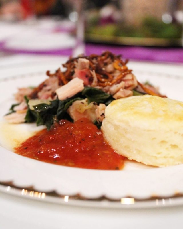 plate of pork, greens, biscuit, and tomato jam