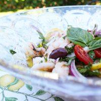 bowl of marinated shrimp, olives, basil