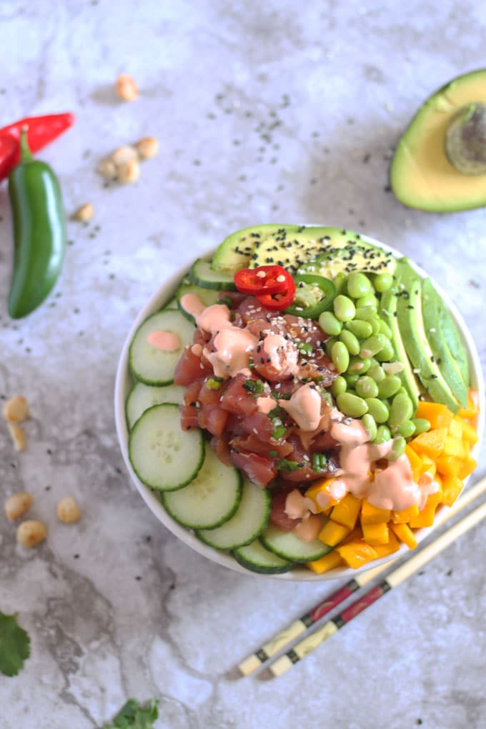 Ahi Tuna Poke Bowl with Citrus Ponzu and Creamy Sriracha Sauce ~ This Hawaiian Style Homemade Poke Bowls are loaded with the freshest citrus ponzu flavored Ahi tuna, rice, cucumbers, avocado, edamame and mango. A drizzle of sriracha sauce and macadamia nuts for crunch are the perfect addition to this Hawaiian favorite.