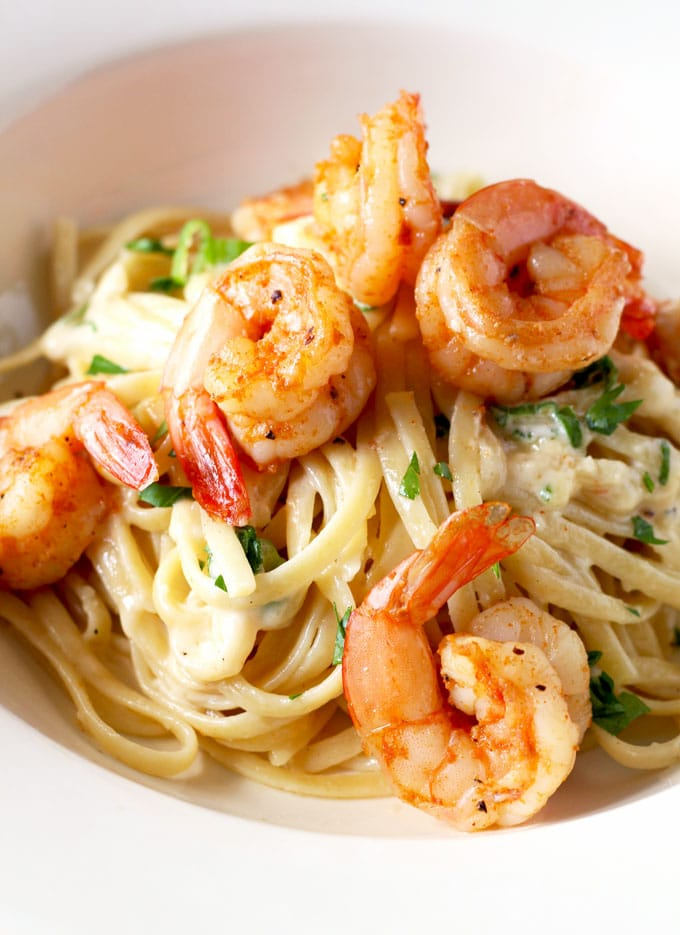 Close up view of a serving of creamy Cajun Shrimp Alfredo Pasta topped with plump Cajun shrimp