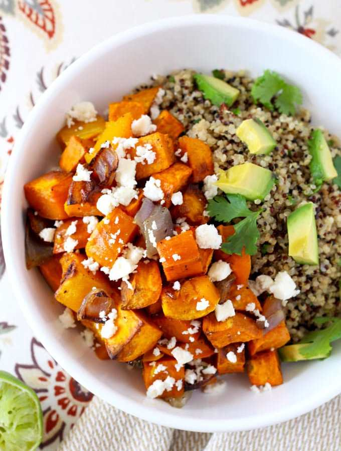 Enjoy this vegetarian Mexican Buddha bowl of perfectly roasted cumin scented butternut squash and sweet potatoes over wholesome cilantro lime quinoa topped with cotija cheese and avocado!