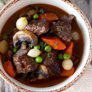 Beef Stew in Red Wine Sauce, tender beef cubes cooked in red wine with onions, garlic, carrots, mushrooms, peas, thyme and bay leaves. The result is a thick, rich, flavorful and out of this world delicious stew. You can cook it in the oven or in the crockpot!