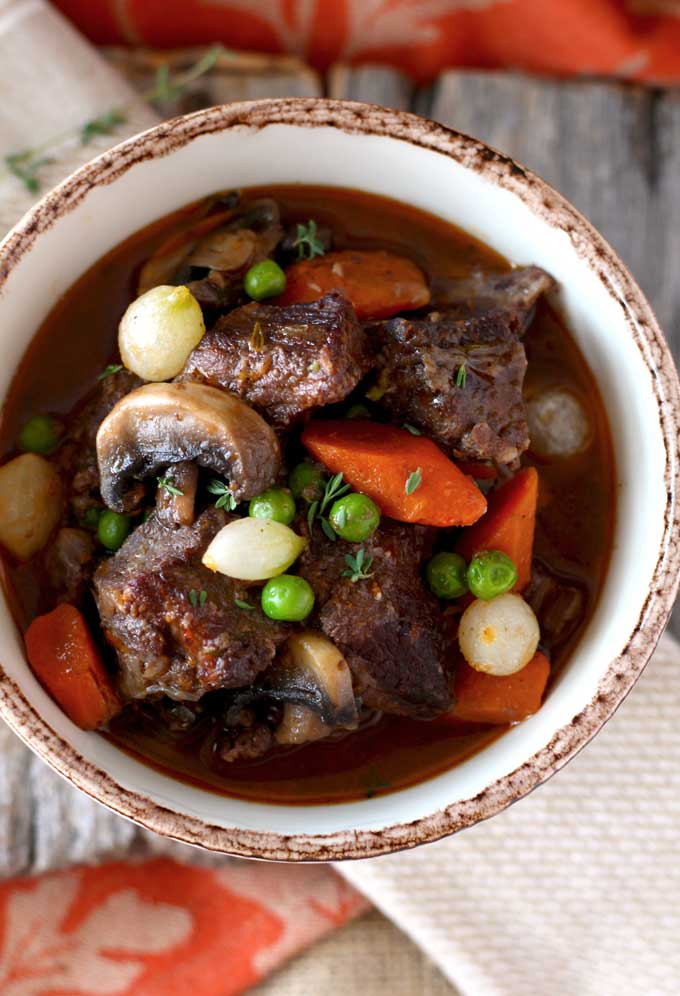 Beef Stew in Red Wine Sauce, tender beef cubes cooked in red wine with onions, garlic, carrots, mushrooms, peas, thyme and bay leaves. The result is a thick, rich, flavorful and out of this world delicious stew. You can cook it in the oven or in the crock pot!