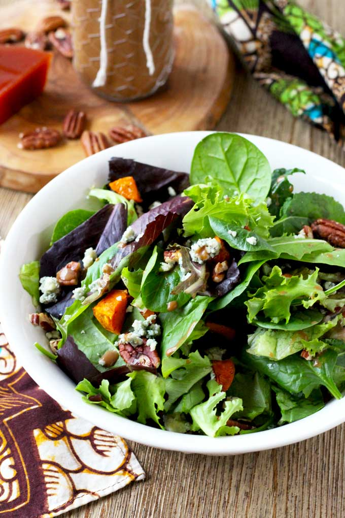 Small pieces of oven roasted sweet potatoes lay on a bed of kale, spinach, radicchio and baby romaine. Toasted pecans add a crunch and creamy blue cheese takes it to the next level of yum! Tossed in a tangy Quince - Balsamic Vinaigrette. This Roasted Sweet Potatoes and Greens Salad with Quince Vinaigrette is unique and delicious!
