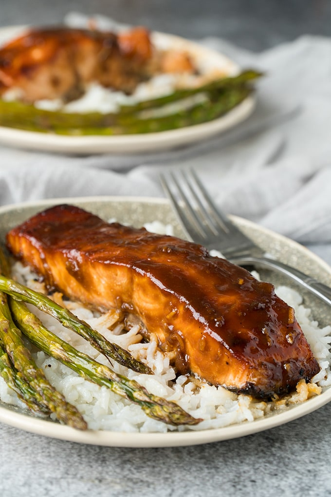 Miso glazed salmon served over rice with asparagus.
