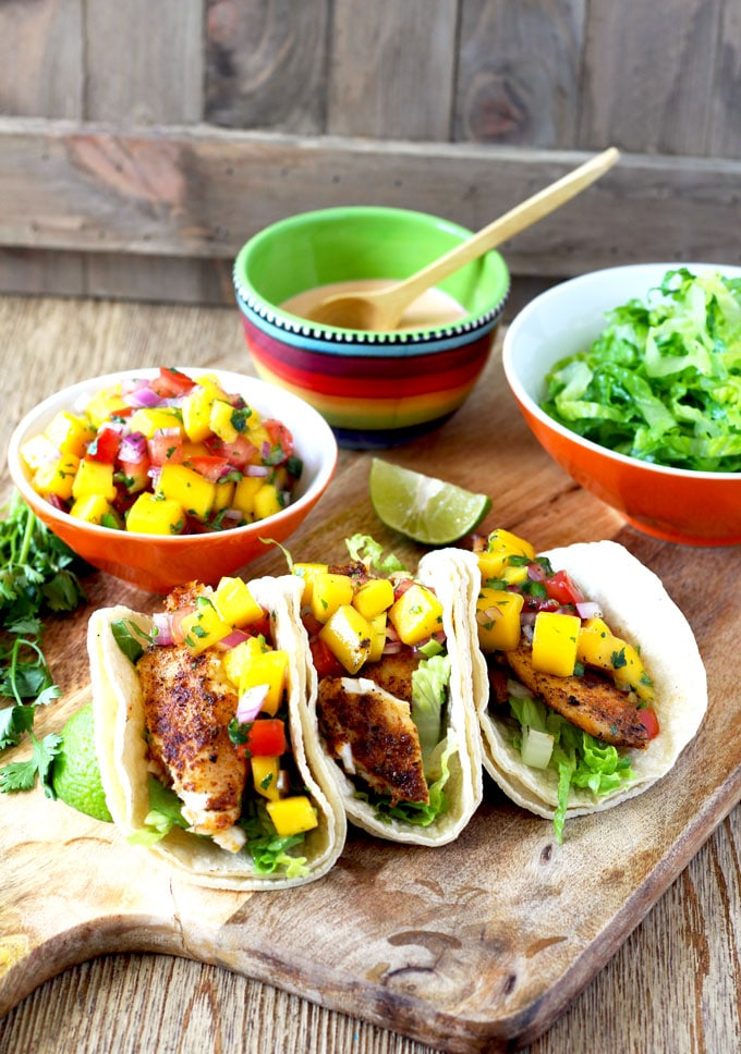Three blackened fish tacos topped with mango salsa on a wooden board