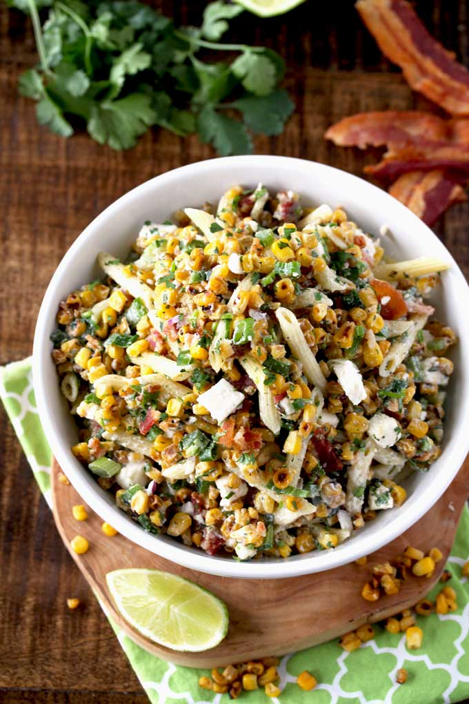 Top view of a bowl of Mexican Street Corn Pasta Salad next to some crispy bacon and limes.
