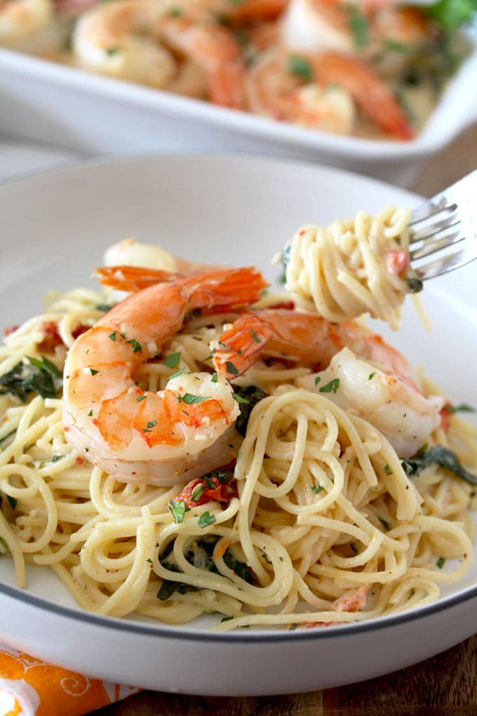 Creamy Tuscan Shrimp over linguine on a white bowl
