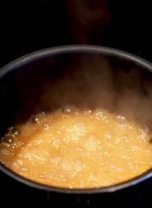 Top view of a pot with caramel bubbling on a stove top.