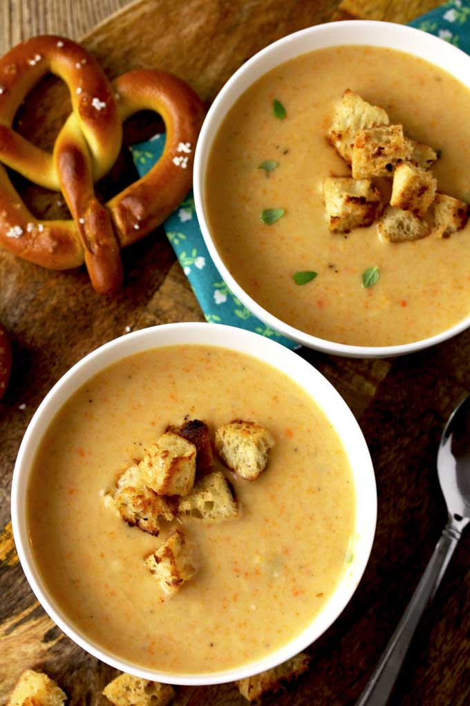 Over view of two white bowls of Cheddar Ale Soup topped with croutons and lightly garnished with thyme leaves. On the side there are two salted pretzels on a wooden board,