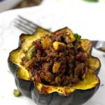 This delicious Stuffed Acorn Squash has a great balance of savory and sweet. Filled with ground beef seasoned with warm spices, dried cranberries, golden raisins, pistachios, parsley and mint. This is the perfect fall and winter dish!