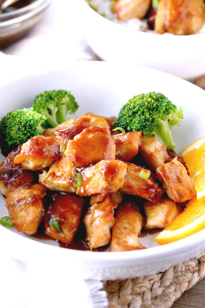 A white bowl filled with orange chicken and broccoli