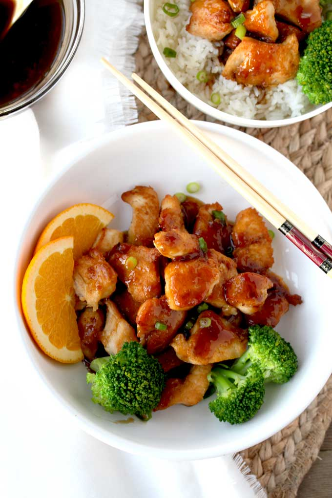 Top view of a white serving bowl with crispy Easy Orange Chicken with broccoli florets and orange slices sitting on a jute place mat.