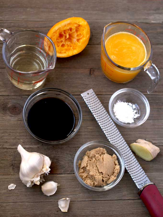 Ingredients to make orange sauce on a wooden surface. A measuring pitcher with orange juice, a measuring pitcher of mirin, a bowl with soy sauce, a small bowl with brown sugar, ginger, garlic and cornstarch. Also a microplane grater