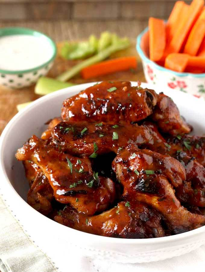 In this photo, view of a white bowl filled with crispy Slow Cooker Chicken Wings tossed in Honey BBQ Sauce on a wooden table. Next theres a small bowl with carrot and celery sticks and a small bowl filled with Ranch dressing.