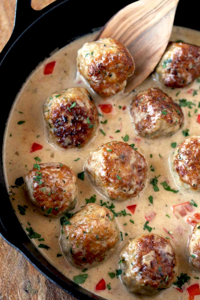 Top view of a skillet with Cajun Chicken Meatballs simmering in creamy sauce. Garnished with chopped parsley.