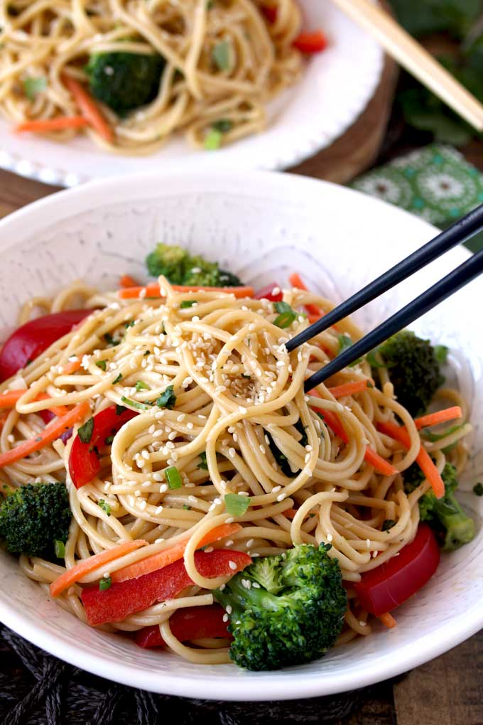 In this photo chopsticks lifting Asian Peanut Sesame Noodles from a big white bowl.